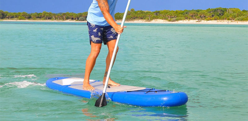 Man standing his Vilano navigator inflatable SUP