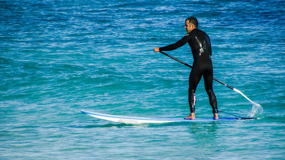 man paddle board in rash guard