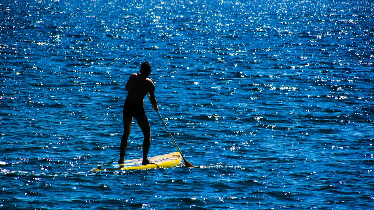 man paddle boarding in the middle of sea