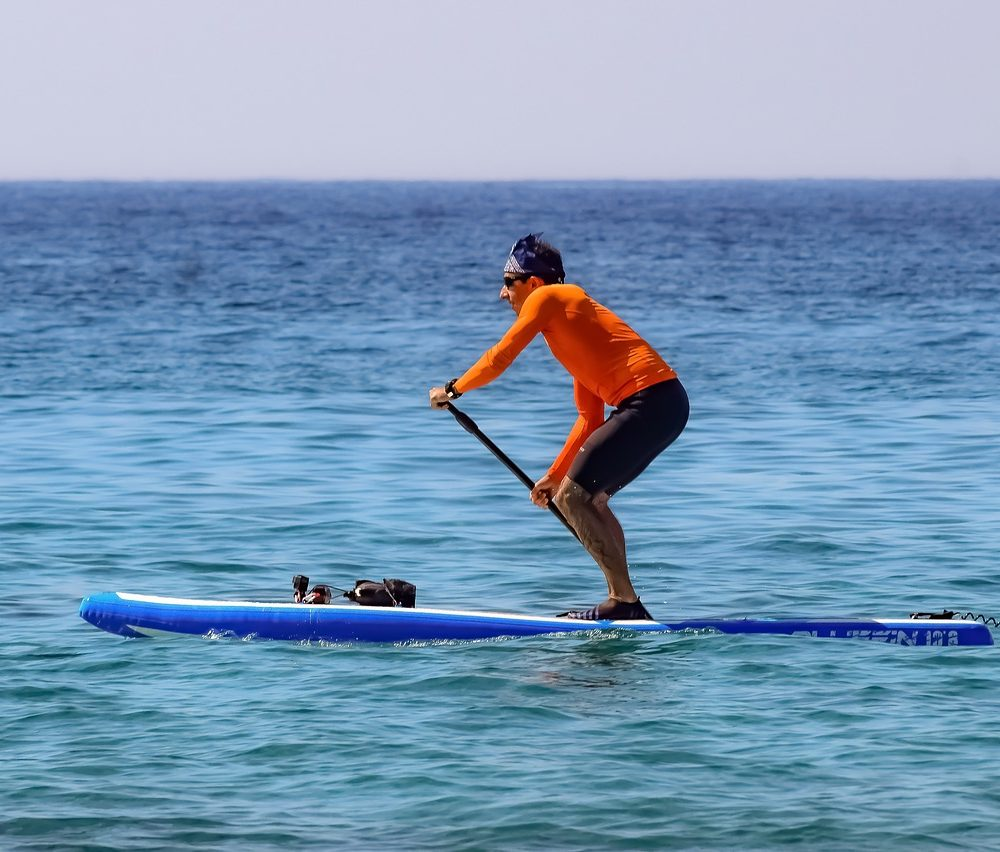 Man Standing In Paddle Board