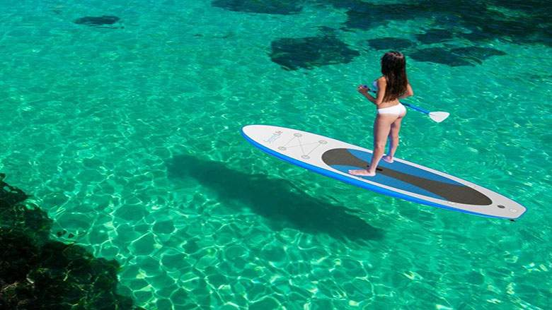 Woman in two piece riding her paddle board