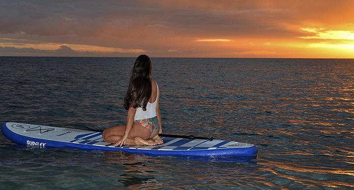 Woman in white riding her paddle board while watching sunrise