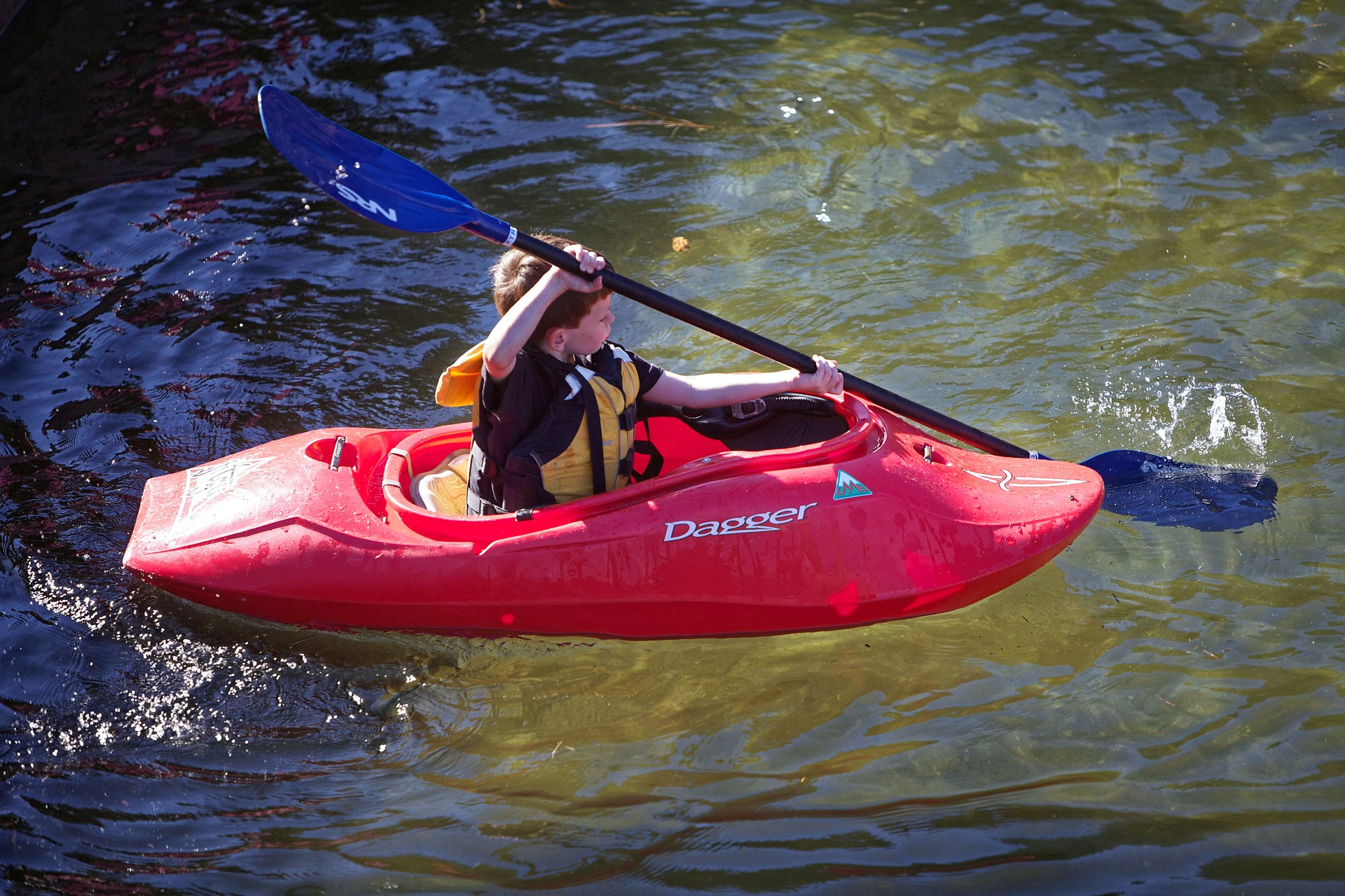 Little boy is paddling the kayak while wearing the best life jackets for kayaking