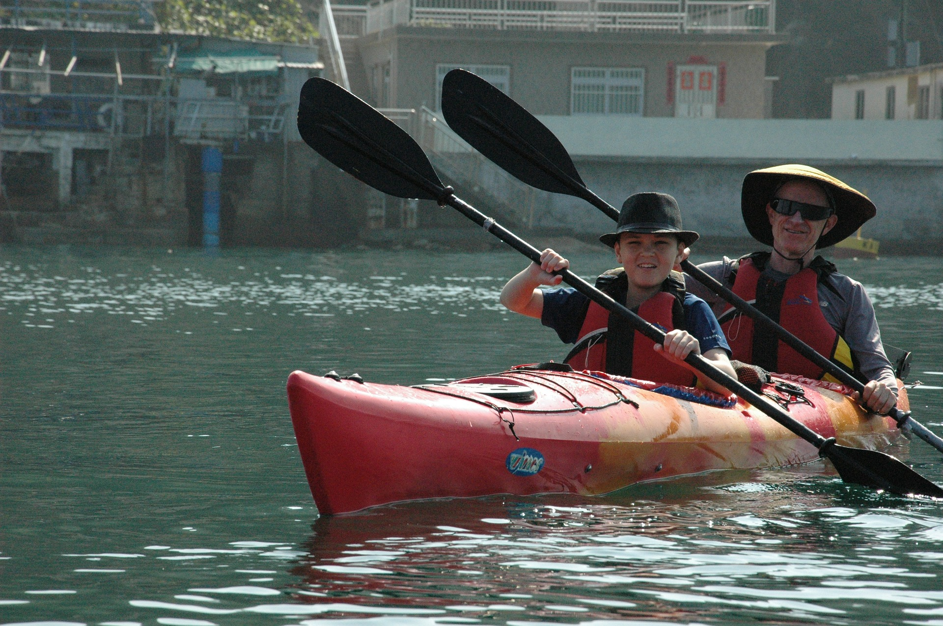 Father and son bonding is to paddle the kayak while wearing a hats and the best life jackets for kayaking