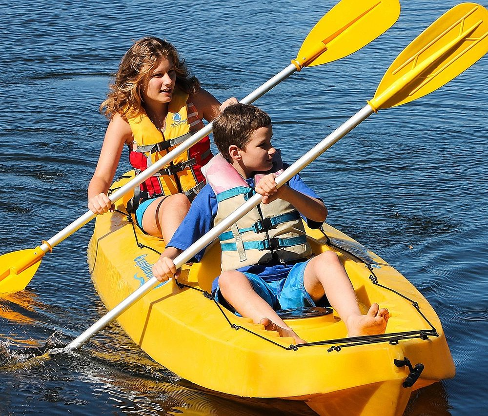 Siblings are paddling the kayak while wearing the best life jackets for kayaking