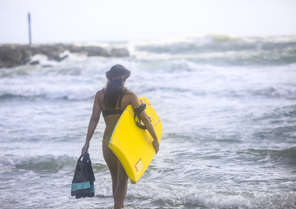 woman with body board and fins learning to ride her boogie board like a pro walking into the waves