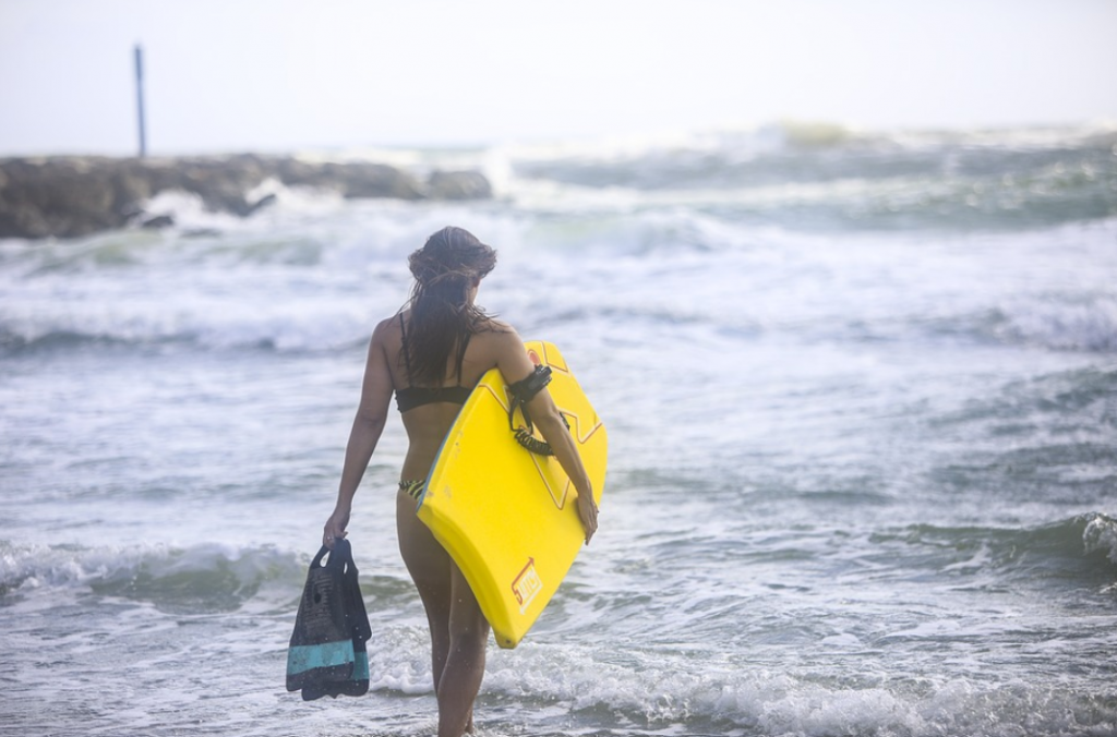 woman with a body board, fins, a leash and learning to ride her boogie board like a pro