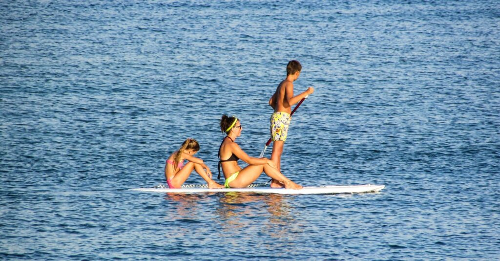 Three people riding on a paddleboard. A boy is standing while a woman and young girl sit